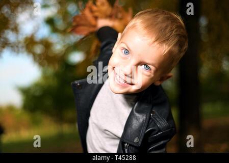 Funny portrait of little sly boy in black leather jacket. autumn season
