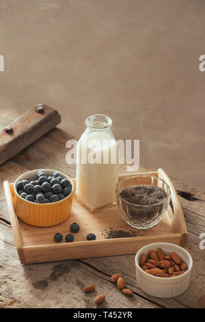 Healthy vegan breakfast. Bottled milk with chia, almond, fresh fruit and berries over wooden table background, copy space. Clean eating, weight loss,  - Stock Photo