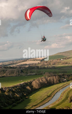 Seaford, East Sussex, UK. 13th Apr 2019. Colder wind from the East brings paraglider pilots to High & Over in the beautiful South Downs overlooking the Cuckmere River. Credit: David Burr/Alamy Live News - Stock Photo