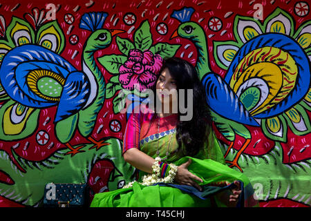 Dhaka, Bangladesh. 14th Apr, 2019. Bangladesh, Dhaka 14 April 2019 - Girl taking a picture in front of the painted wall also come to attend a rally to celebrate the Bengali New Year or 'Pohela Boishakh 1426' in Dhaka. People attend with colorful clothes in 'Pohela Boishakh', which falls every year on April 14 in Bangladesh. Credit: KM Asad/ZUMA Wire/Alamy Live News - Stock Photo