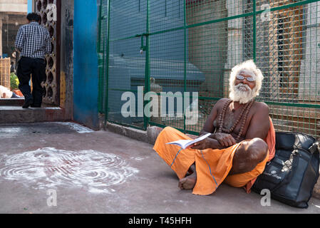 Horizontal portrait of an old Sadhu sitting at the gates of the Kapaleeshwarar Temple in Chennai, India. - Stock Photo