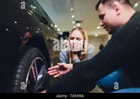 Young couple choosing new car for buying in dealership shop. - Stock Photo