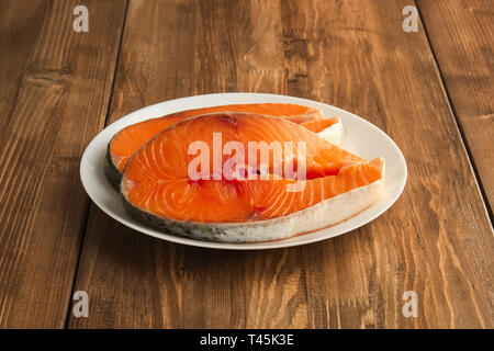 Two pieces of fresh salmom steak on a plate on wooden table - Stock Photo