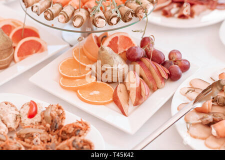 plate with slices of various fruits on the festive table - Stock Photo