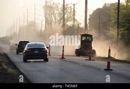 BOSSIER CITY, LA., U.S.A. - APRIL 12, 2019: A worker raises a cloud of dust dramatically backlighted by the setting sun as work proceeds on a U.S. Hig - Stock Photo