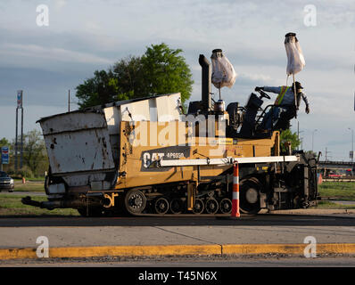 BOSSIER CITY, LA., U.S.A. - APRIL 12, 2019: A worker operates a piece of heavy equipment as work proceeds on a U.S. Highway 80 repaving project. - Stock Photo