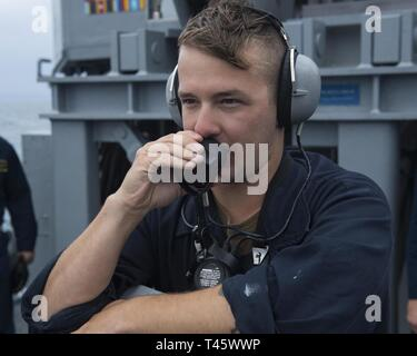 OKINAWA, Japan (March 09, 2019) Mineman Seaman Curtas Veltre uses a sound powered telephone on the fo'c'sle of the Avenger-class mine countermeasures ship USS Pioneer (MCM 9). Pioneer, part of Mine Countermeasure Squadron 7, is operating in the U.S. 7th Fleet area of operations to enhance interoperability with partners and serve as a ready-response platform for contingency operations. - Stock Photo