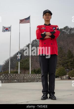 Sgt. Chanidapa Suksiripornrit, culinary specialist assigned to 61st Support Maintenance Company, 194th Combat Sustainment Support Battalion, 2nd Sustainment Brigade, an Alexandria, Va. native (originally from Bangkok, Thailand), stands proudly for a photograph in honor of Women's History Month, Camp Casey, March 10, 2019. Suksiripornrit took time out of her day at the 210th Field Artillery Brigade Thunder Inn dining facility (DFAC) to pose for a photo in front of the United States and Republic of Korea flags and the 2nd Infantry Division Indianhead patch. September 2008, at age 11, Suksiriporn - Stock Photo