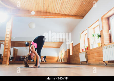 Young attractive sporty woman practicing yoga, standing forward bend exercise, head to knees, uttanasana pose, working out, wearing sportswear, white - Stock Photo