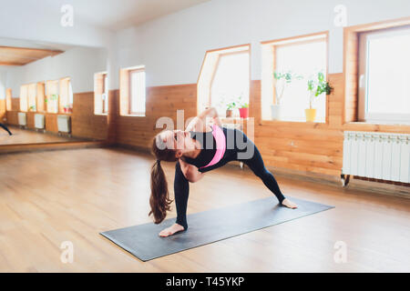 Rear view of young female yogi in sports bra and leggings doing bound extended side angle pose, baddha utthita parsvakonasana, while practicing yoga - Stock Photo