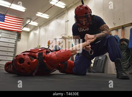 Petty Officer 2nd Class William Viera, a storekeeper assigned to Coast Guard Station Juneau, practices takedown and handcuff techniques while attending boarding team member training at Station Juneau Feb. 28, 2019. Qualified Station Juneau personnel provided BTM training to more than 10 Juneau area Coast Guard members. U.S. Coast Guard - Stock Photo
