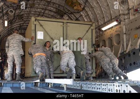 A team of Reserve Citizen Airmen from the 48th Aerial Port Squadron and Hawaii Air National Guard loadmasters load equipment onto a U.S. Air Force C-17 Globemaster III aircraft during an aeromedical staging and aerial port training at Joint Base Pearl Harbor-Hickam, Hawaii, March 3, 2019. The event was a collaborative effort to build working relationships between the Hawaii Air National Guard and Air Force Reserve and focused on both medical and aerial port functions, to include enroute patient care and staging, and cargo preparation and loading. - Stock Photo