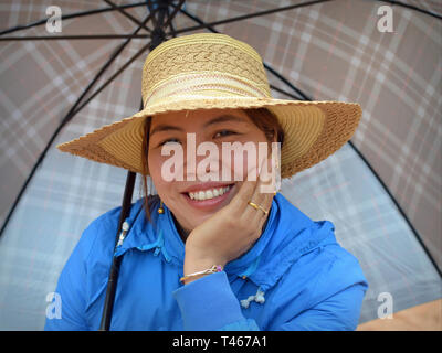 Smiling Vietnamese woman wears a stylish straw hat and poses for the camera with a large stick umbrella. - Stock Photo