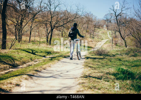 Cycling in nature. Rear view young woman walks beside her bike up hill in woods on sunny spring day. - Stock Photo