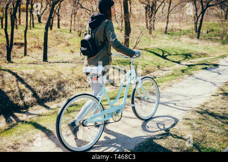 Rear view full height portrait of young woman walking beside bicycle on nature path on sunny spring day. - Stock Photo
