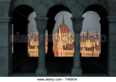 The Sun Sets Across the Hungarian Parliament Building Seen Through the Struts of Fisherman`s Bastion - Stock Photo