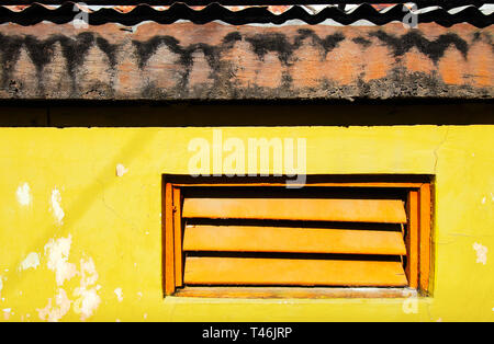 Orange colored window shutters in a bright yellow painted wall with dark shadows from the wooden roof with corrugated metal sheets - Stock Photo