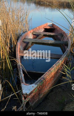 Lonely old wooden fishing boat on autumn lake coast with rain water - Stock Photo