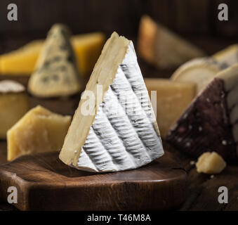 Segment of  Brie cheese or soft cow's - milk  French cheese on wooden board. Different cheeses at the background. - Stock Photo