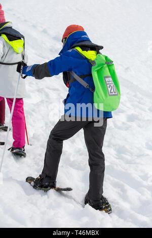 Chinese tourists snow shoeing at Orne Harbour on the Danco coast, Graham Land, Antarctic Peninsular. - Stock Photo