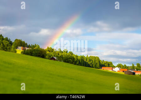 Rainbow near the house. Traditional colored wooden house in Norway at summer day. Country houses in village in Norway. - Stock Photo