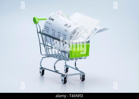 Shopping cart with receipt , concept for grocery expenses and consumerism - Stock Photo