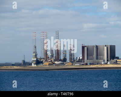 Jack Up drilling rigs at the TERRC Hartlepool  facility on the river Tees for storage  and repair by Hartlepool Nuclear Power Station - Stock Photo