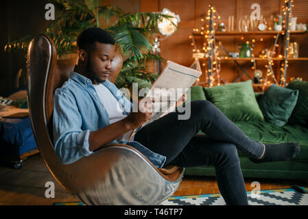 Black man reading newspaper in a comfortable chair
