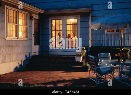 Family Inside Suburban House Seen through French Doors from Patio, USA - Stock Photo