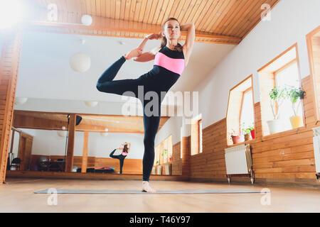 beautiful woman doing yoga dancing pose standing on one