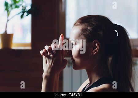 Beautiful young caucasian woman doing face yoga pose.