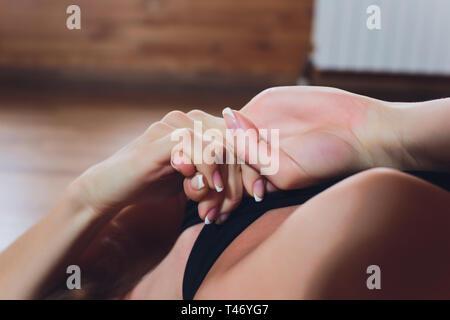 Beautiful young woman practices yoga asana Gomukhasana - Cow face pose at the yoga studio. - Stock Photo