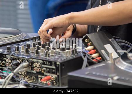 female hand playing DJ mixer - Stock Photo