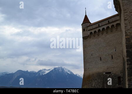 Medieval turret and wall of Chillon Castle, Montreux, Switzerland, on a cloudy day in Spring (April) on Lake Geneva against snowy mountain backdrop - Stock Photo