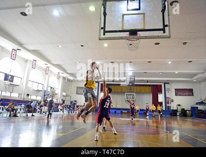 MANILA, Philippines (March 15, 2019) - Boatswain's Mate 2nd Class Tyjhay McCain, from South Bend, Ind., attempts a lay up during a goodwill basketball game between U.S. 7th Fleet Flagship USS Blue Ridge (LCC 19) and the Colegio de San Juan, Letran Knights in Manila, Philippines. Blue Ridge is the oldest operational ship in the Navy and, as 7th Fleet command ship, actively works to foster relationships with allies and partners in the Indo-Pacific Region. - Stock Photo