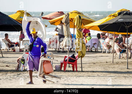Cartagena Colombia El Laguito Hispanic resident residents man Caribbean Sea public beach umbrellas carrying rental chairs sand - Stock Photo