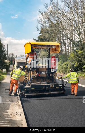 Presteigne, Powys, Wales, UK. An asphalt paver or paving machine laying fresh tarmac on a road in the town - Stock Photo