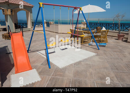 Childrens play area playground on large roof terrace patio area with panoramic tropical sea view - Stock Photo