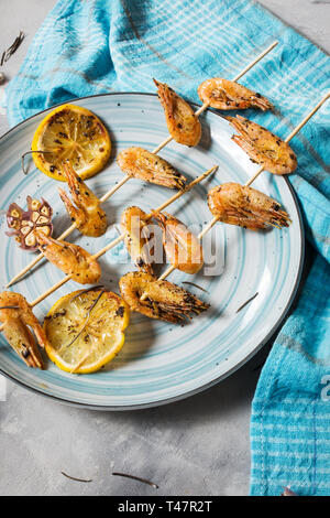 Grilled shrimp skewers with herbs, garlic and lemon on concrete background. Seafood, shelfish. - Stock Photo