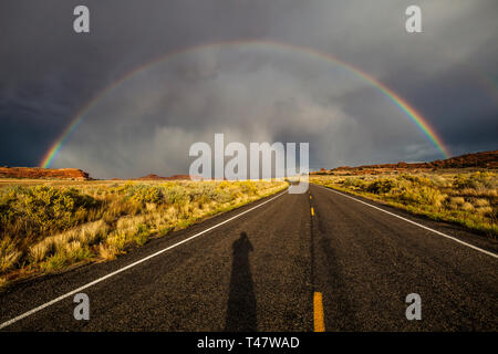 The shadow of the photographer shows on the road below a full rainbow and thuderstorm clouds over Scenic Highway 211 in Canyonlands National Park, Sou - Stock Photo