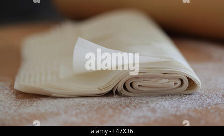 Closeup of homemade fillo pastry isolated on floured table.Rolling pin on blurred background - Stock Photo