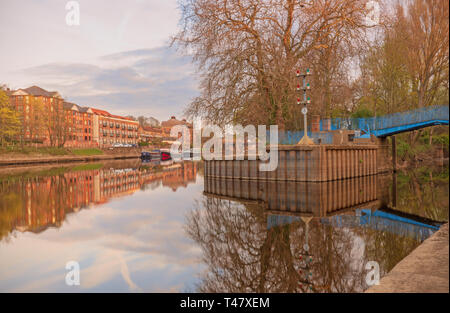 Dawn at the confluence of the River Ouse and River Foss in York.  Apartment buildings are reflected in the water and a footbridge is in the foreground. - Stock Photo