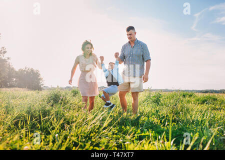 Mother and father swinging son in sunnny summer day on meadow - Stock Photo