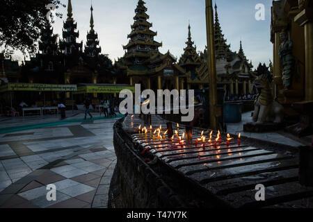 Yangon, Myanmar - 19 September 2016: Candles burning at Shwedagon Pagoda - Stock Photo