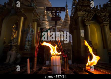Yangon, Myanmar - 19 September 2016: Candles burning while people bathe a statue of Buddha at Shwedagon Pagona - Stock Photo