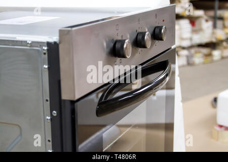 Built-in stainless steel electric oven in a furniture store on a shop window against the backdrop of a bright furniture warehouse, soft focus. - Stock Photo