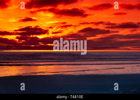Red. orange and yellow sunset over beach with gently rolling waves breaking onto shore. - Stock Photo