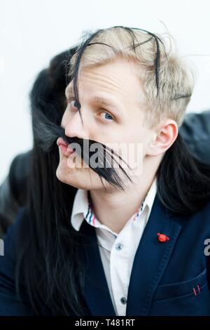 Blond man in formal dress making funny grimace with fake mustache from black girlfriend's hairs. - Stock Photo