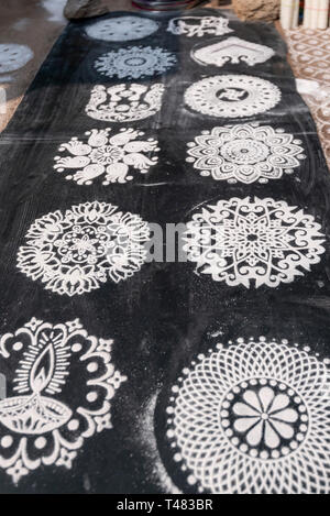 Vertical view of rangoli patterns on the roadside in India. - Stock Photo