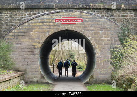 walkers on the John Muir Way on Strathkelvin Railway Walkway passing through the old railway tunnel next to Milton of Campsie railway station Scotland - Stock Photo